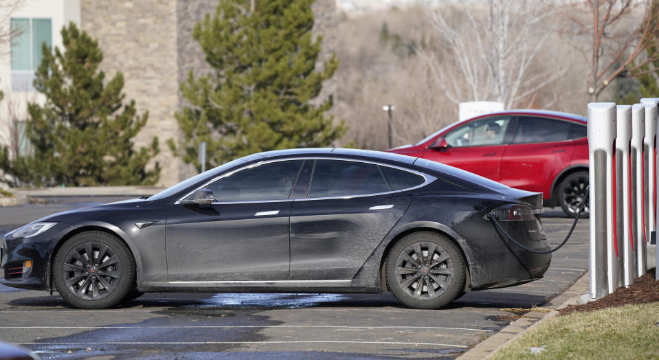A Tesla Model S, front, and Model Y charge at a Tesla supercharging site outside Colorado Mills outlet mall late Monday, Dec. 21, 2020, in Lakewood, Colo. (AP Photo/David Zalubowski)