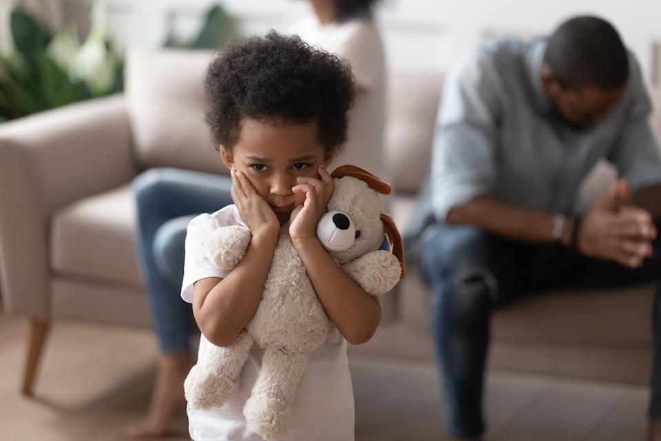 On foreground close up focus on african lonely boy embraces soft toy as symbol seeking for protection support, son closed ears not to hear parents scandal, divorce negative affect to children concept