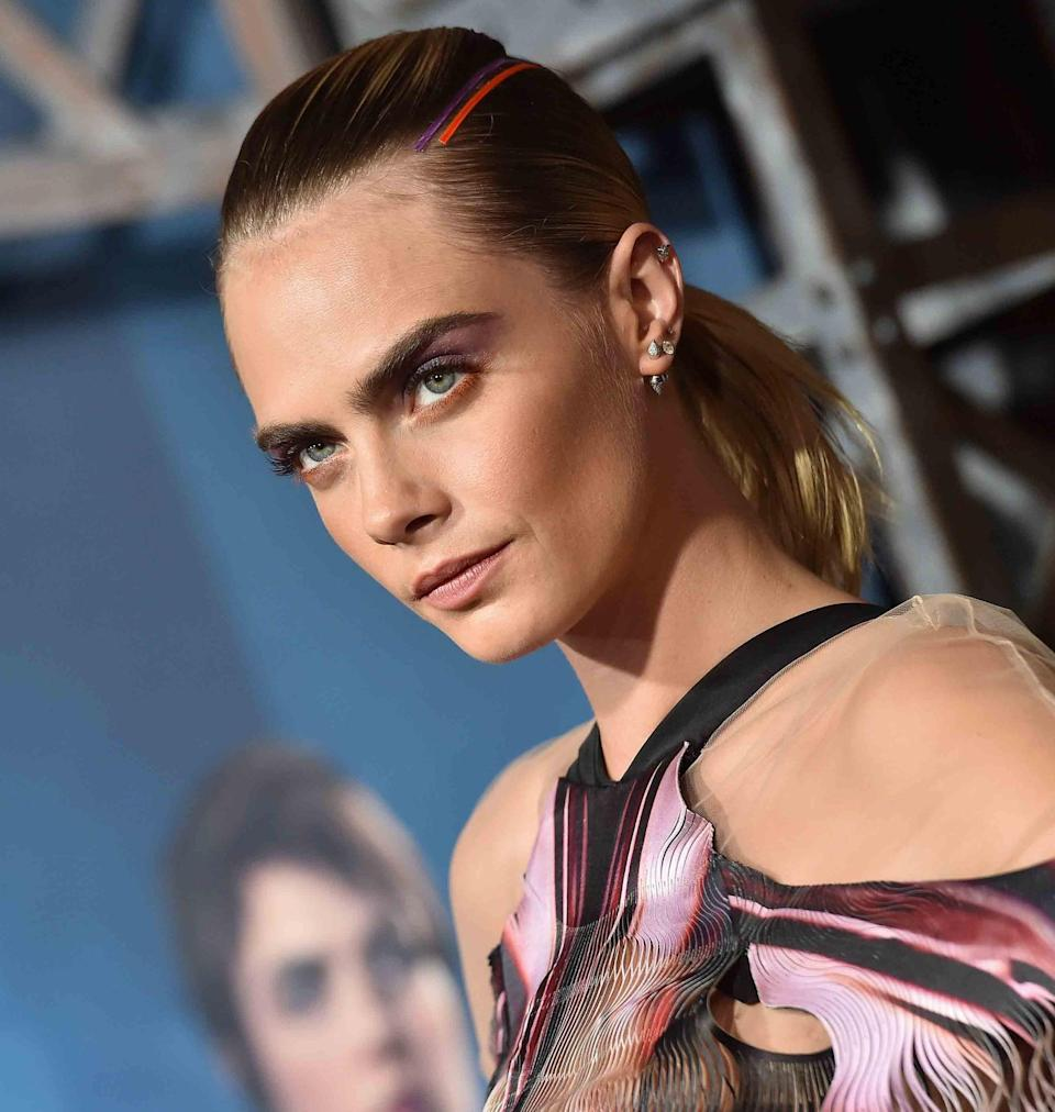"""<p><a href=""""https://www.popsugar.com/beauty/Cara-Delevingne-Ribbon-Hairstyle-Carnival-Row-2019-46529335"""" class=""""link rapid-noclick-resp"""" rel=""""nofollow noopener"""" target=""""_blank"""" data-ylk=""""slk:For the Los Angeles premiere of Delevingne's new show"""">For the Los Angeles premiere of Delevingne's new show</a>, <strong>Carnival Row</strong>, Roszak got crafty, stopping at a haberdashery store in Beverly Hills to buy orange and lilac ribbon to match both the actor's Iris van Herpen dress and orange-and-lilac eye shadow by makeup artist Molly Stern. After creating a double ponytail (one secured at the crown of the head and one at the nape of the neck), Roszak adhered strips of the purple and orange ribbons along the parts on either side of Delevingne's head almost like racing stripes, giving the overall look a graphic, sporty sort of vibe.</p>"""