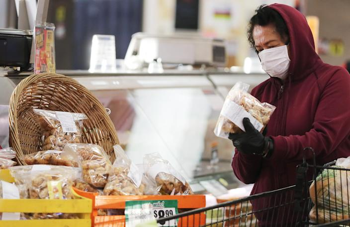 A shopper wears a face mask while picking out groceries during special hours open to seniors at Northgate Gonzalez Market in Los Angeles. (Mario Tama/Getty Images)