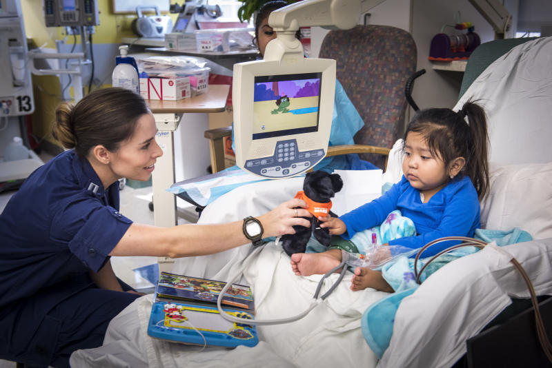 Cook hands a plush toy to a dialysis patient at the hospital on Labor Day.  (Allen S Kramer/Texas Childrens Hospital)