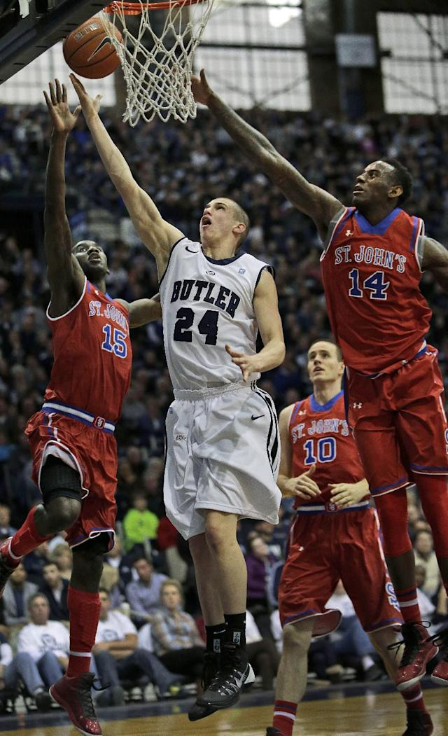 Butler guard Kellen Dunham (24) shoots between St. John's defenders Sir'Dominic Pointer (15) and Jakarr Sampson (14) during the first half of an NCAA college basketball game, Saturday, Jan. 25, 2014, in Indianapolis. (AP Photo/AJ Mast)