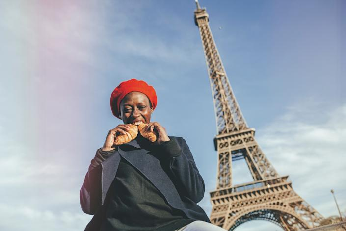 France, Paris, young woman eating two croissants in front of Eiffel Tower