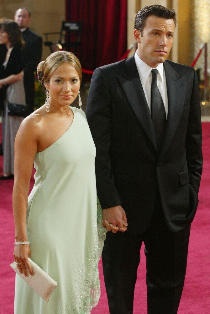 Jennifer Lopez and Ben Affleck attend the Academy Awards. She wears a light green on shouldered dress with statement jewellery.