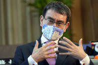 FILE - In this July 28, 2021, file photo, Taro Kono, Japan's minister in charge of a huge vaccination campaign, speaks during an interview with The Associated Press at his office in Tokyo. Kono promised Sunday, Aug. 29, 2021 a timely administering of booster shots for the coronavirus, as the nation aims to fully vaccinate its population by October or November. (AP Photo/Eugene Hoshiko, File)