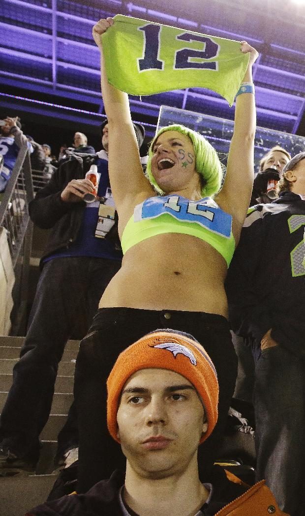 A Denver Broncos fan reacts as a Seattle Seahawks fan cheers during the second half of the NFL Super Bowl XLVIII football game Sunday, Feb. 2, 2014, in East Rutherford, N.J. (AP Photo/Mel Evans)