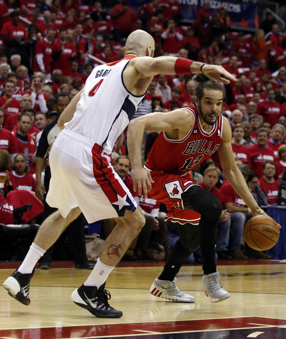 Chicago Bulls center Joakim Noah (13) drives past Washington Wizards center Marcin Gortat (4), from Poland, in the first half of Game 3 of an opening-round NBA basketball playoff series on Friday, April 25, 2014, in Washington. (AP Photo/Alex Brandon)