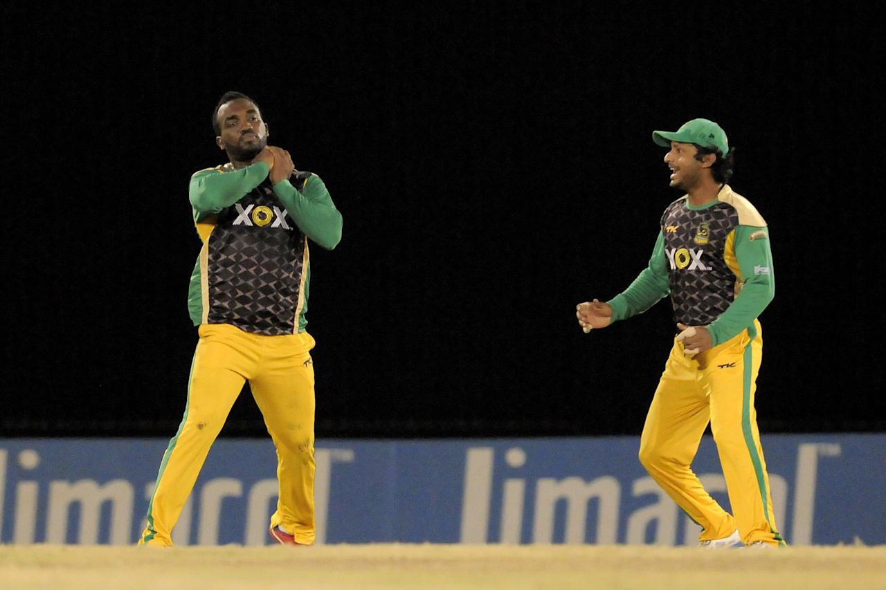 PORT OF SPAIN, TRINIDAD AND TOBAGO - AUGUST 24:  Danza Hyatt (L) of Jamaica Tallawahs catching Guyana Amazon Warriors William Perkins and Kumar Sangakkara (R) celebrates during the Final of the Caribbean Premier League between Guyana Amazon Warriors v Jamaica Tallawahs at Queens Park Oval on August 24, 2013 in Port of Spain, Trinidad and Tobago. (Photo by Randy Brooks/Getty Images Latin America for CPL)