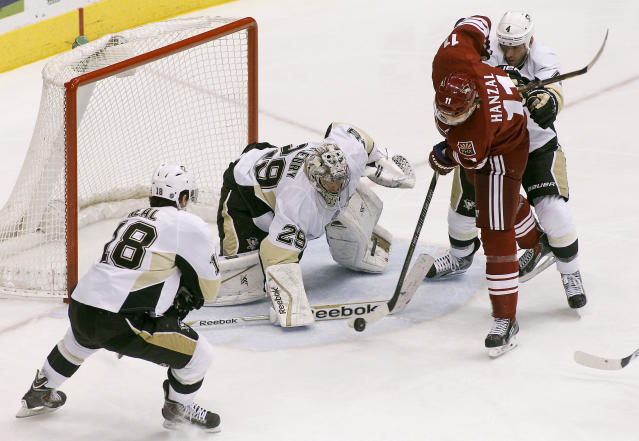 Phoenix Coyotes' Martin Hanzal (11) attempts to get a shot off on Pittsburgh Penguins goaltender Marc-Andre Fleury (29) as Penguins' James Neal (18) and Rob Scuderi (4) defend during the second period of an NHL hockey game on Saturday, Feb. 1, 2014, in Glendale, Ariz. (AP Photo/Ralph Freso)