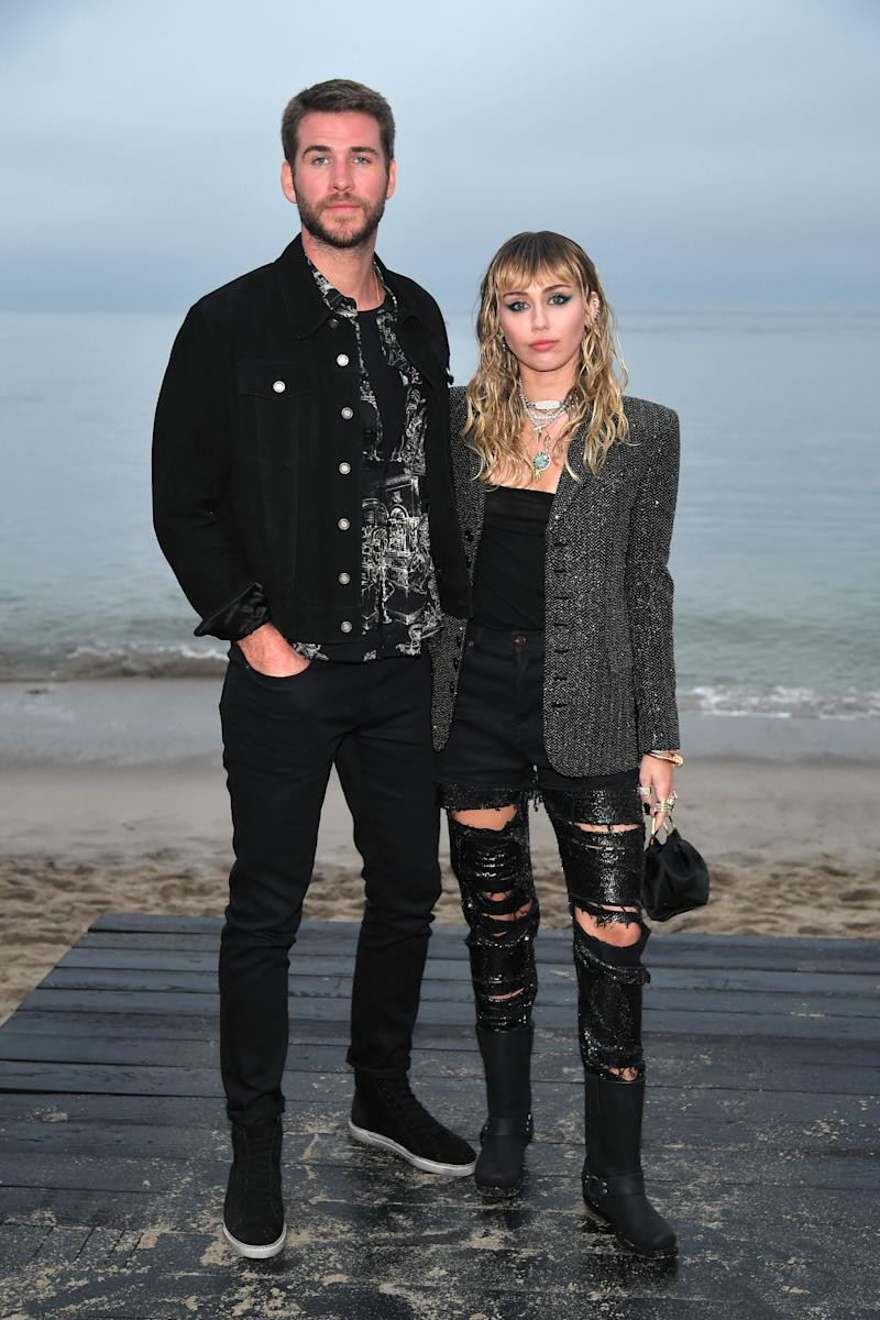 Miley Cyrus and Liam Hemsworth in black clothes at the beach