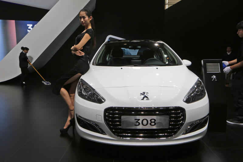 In this Nov. 21, 2013 photo, a model poses by a Peugeot 308 at the company's booth during the Guangzhou 2013 Auto Show in China's southern city of Guangzhou. French automakers Peugeot and Renault are looking belatedly to China to revive their flagging fortunes but picked a tough time to try to expand. France's biggest auto brand, PSA Peugeot Citroen, in China since the '80s without carving out significant market share, said it will be more aggressive after its local partner, Dongfeng Motor Co., in the week of Feb. 16, 2014 agreed to take a 14 percent stake in PSA. (AP Photo/Kin Cheung)