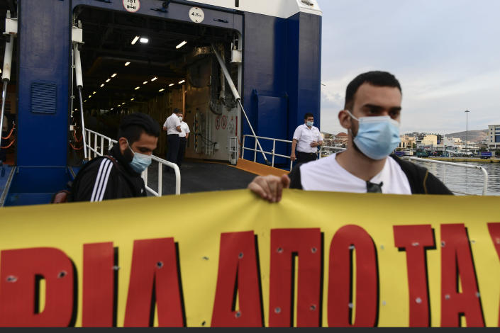 Protesters block the entrance of a passenger ship during a 24-hour labour strike at the port of Piraeus, near Athens, Thursday, June 10, 2021. Greece's biggest labor unions stage a 24-hour strike to protest a draft labor bill being debated in parliament, which workers say will erode their rights. (AP Photo/Michael Varaklas)
