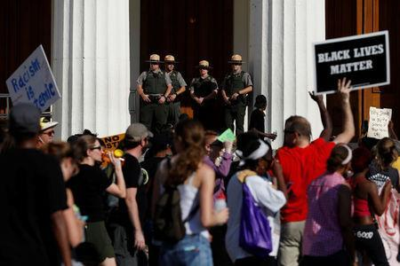 Members of National Park Service watch as protesters pass the Old Courthouse after the not guilty verdict was announced in the murder trial of Jason Stockley, a former St. Louis police officer, charged with the 2011 shooting of Anthony Lamar Smith, in St. Louis, Missouri, U.S., September 15, 2017. REUTERS/Whitney Curtis