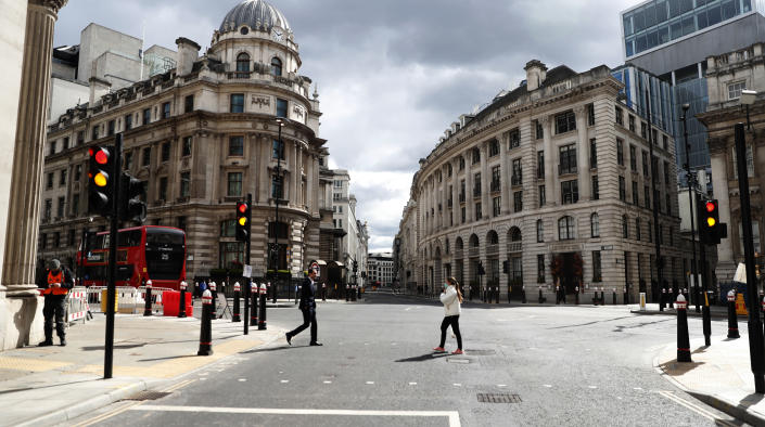 People cross the road at Bank junction in the City of London, Tuesday, April 6, 2021. When the pandemic struck, about 540,000 workers vanished from London's financial hub almost overnight. A year on, most haven't returned to the business hub. (AP Photo/Alastair Grant)