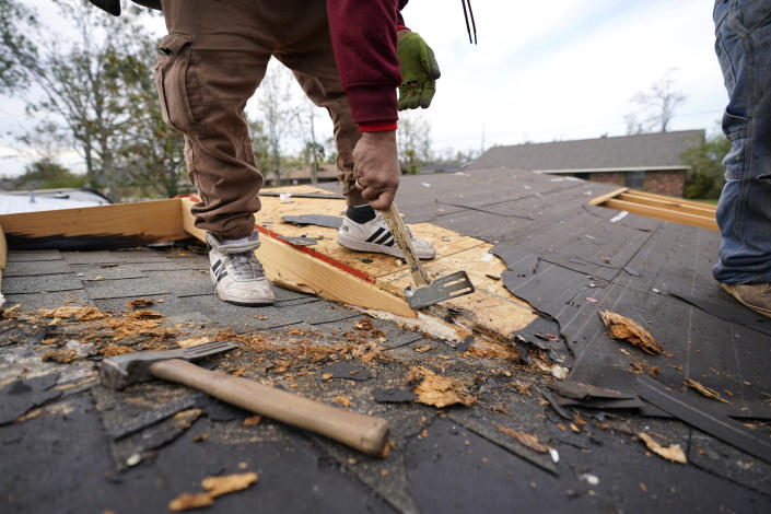 Roofers work on the heavily damaged and gutted home of Christi and Brandy Monticello, in the aftermath of Hurricane Laura and Hurricane Delta, in Lake Charles, La., Friday, Dec. 4, 2020. (AP Photo/Gerald Herbert)