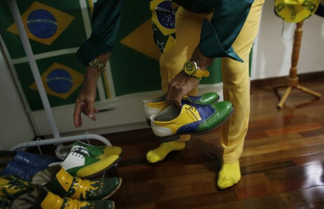 Brazilian attorney, Nelson Paviotti, gets dressed in one of his many outfits with the colors of the national flag - green, yellow, white and blue, at his home in Campinas, Sao Paulo state, April 9, 2014. Paviotti claims he has worn clothes of only those colors as he promised to do if Brazil won the 1994 World Cup, which it did. He has recently decorated his home specially for the 2014 World Cup that Brazil is hosting. Picture taken April 9, 2014. REUTERS/Nacho Doce (BRAZIL - Tags: SPORT SOCCER SOCIETY)