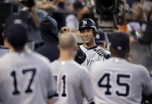New York Yankees' Derek Jeter celebrates after scoring on a Mark Teixeira double against the Detroit Tigers in the third inning of a baseball game in Detroit, Wednesday, Aug. 27, 2014. (AP Photo/Paul Sancya)