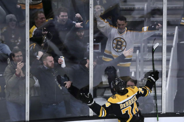 Boston Bruins left wing Jake DeBrusk (74) celebrates with fans after his game-tying goal against Vegas Golden Knights goaltender Marc-Andre Fleury during the third period of an NHL hockey game in Boston, Tuesday, Jan. 21, 2020. (AP Photo/Charles Krupa)