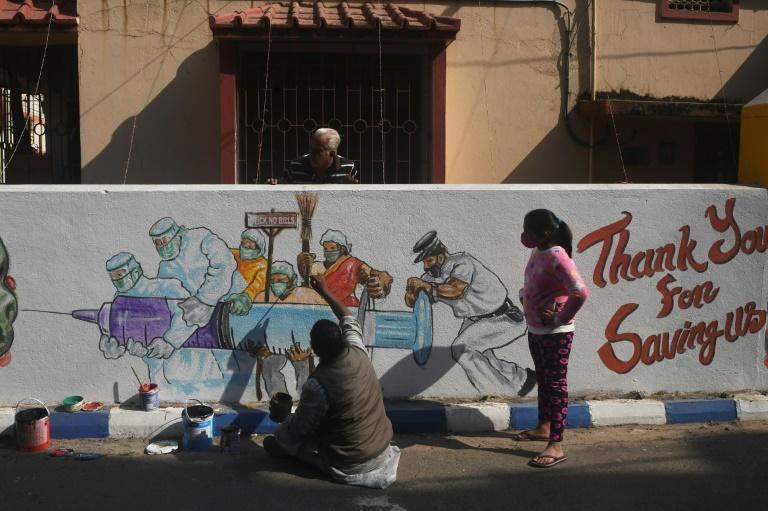 An artist puts finishing touches on a mural depicting frontline workers carrying a vaccine in Kolkata on January 2, 2021