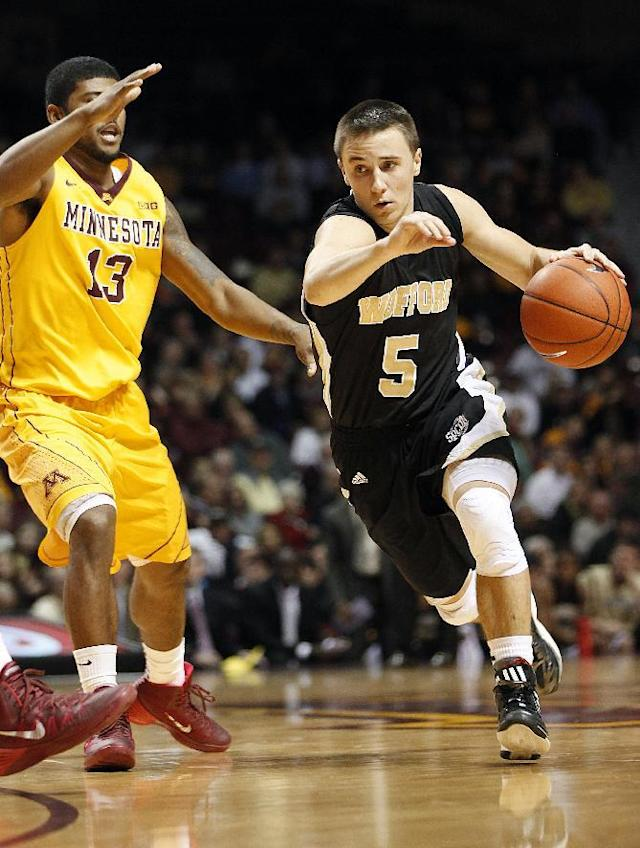 Wofford guard Eric Garcia (5) pushes the ball down the court past Minnesota guard Maverick Ahanmisi (13) in the first half of an NCAA college basketball game Thursday, Nov. 21, 2013, in Minneapolis. (AP Photo/Stacy Bengs)