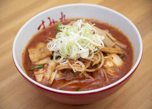 The thick soup is filled with many toppings such as onions, garlic chives, bean sprouts and thinly sliced pork belly.