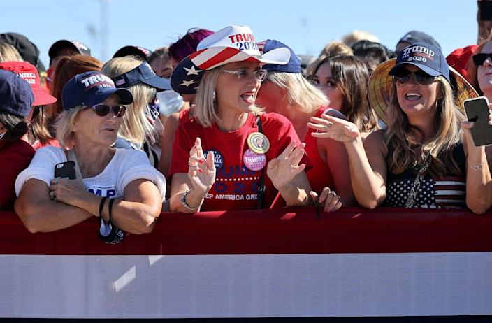Three middle-aged women at a rally wearing Trump hats.