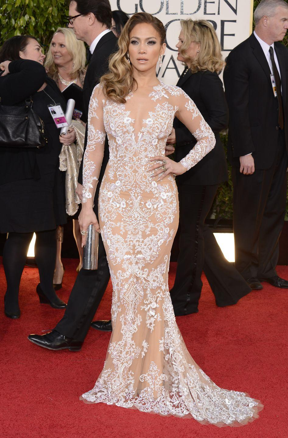 <p>J.Lo stuns in this figure-hugging lace Zuhair Murad dress at the Golden Globes. She pairs the look with a metallic clutch and completes it with a regal wavy 'do pulled over to one side.</p>
