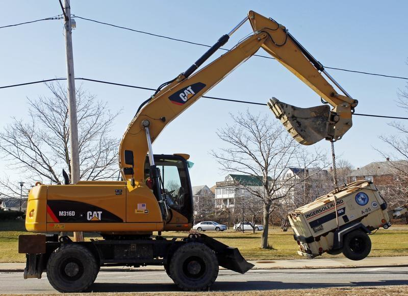 A Caterpillar tractor lifts a piece of construction equipment in Somerville
