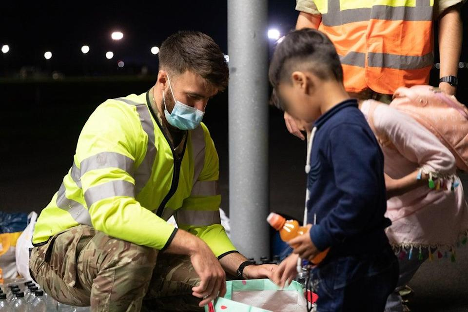 Military personnel handing out food, drink, toys, and blankets during Operation Pitting at RAF Brize Norton to arrivals who have been evacuated from Afghanistan. (Cpl Will Drummee RAF/MOD/Crown copyright) (PA Media)