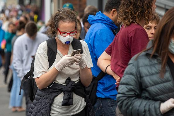 A woman in a mask is seen lining up at Centrelink in Bondi Junction in Sydney, Australia.