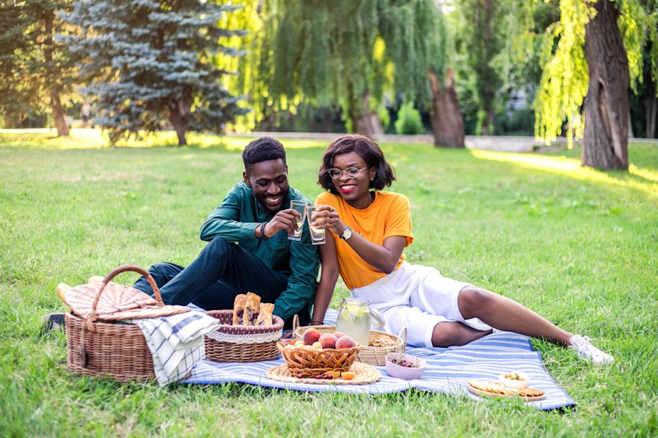 Young happy black couple on picnic in the park.