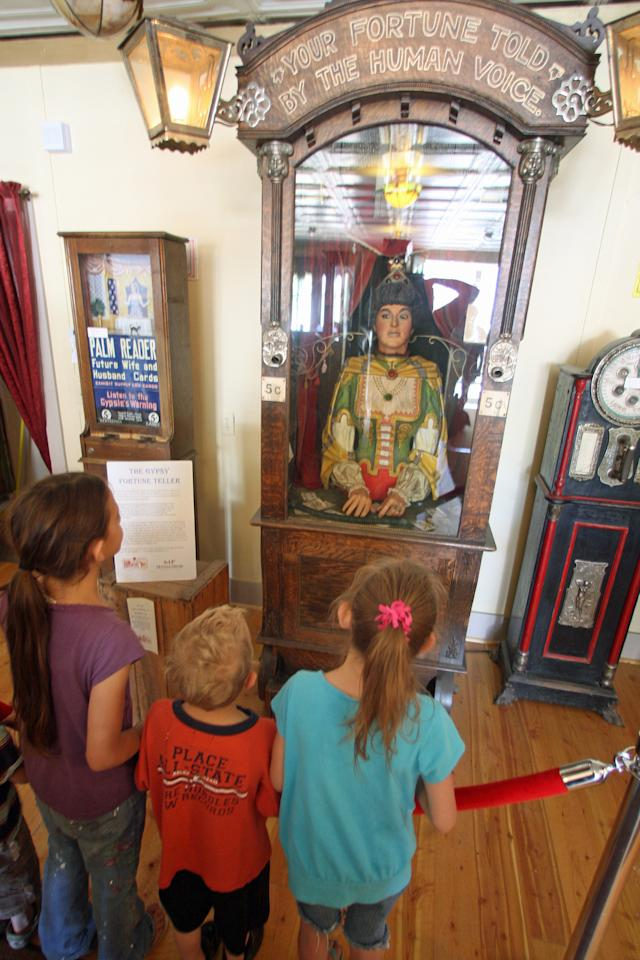 In this July 28, 2011 photo, children stand in front of an antique Gypsy fortune teller machine, that sat for decades in a Virginia City, Mont., restaurant and has received multimillion dollar offers from curators including magician David Copperfield. Collectors say the 100-year-old machine that speaks your fortune may be the last of its kind. (AP Photo/Michael Albans)