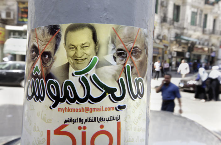 """Egyptians walk near a poster showing ousted president Hosni Mubarak, center, and presidential candidates Amr Moussa, left, Mubarak's foreign minister for 10 years, and Ahmed Shafiq, a former Air Force commander and civil aviation minister whom Mubarak made prime minister during his last days in power, with Arabic that reads, """"they will not rule,"""" in Cairo, Egypt, Monday, May 21, 2012. The May 23-24 presidential election is the first since last year's ouster of longtime authoritarian ruler Hosni Mubarak. It marks the first time Egyptians will choose their leader in a race overseen by international monitors. (AP Photo/Amr Nabil)"""