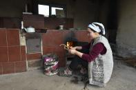 Zarina, wife of Azret Kaliyev, son of Kanat Kaliyev, kindles a fire in the hearth for cooking at the family house in Tash Bashat village about 24 kilometers (15 miles) southeast of Bishkek, Kyrgyzstan, Tuesday, Oct. 20, 2020. Kyrgyzstan, one of the poorest countries to emerge from the former Soviet Union, where political turmoil has prompted many people to have little respect for authorities, whom they see as deeply corrupt.(AP Photo/Vladimir Voronin)