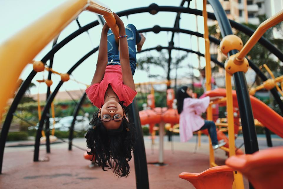 Girl upside down on the jungle gym