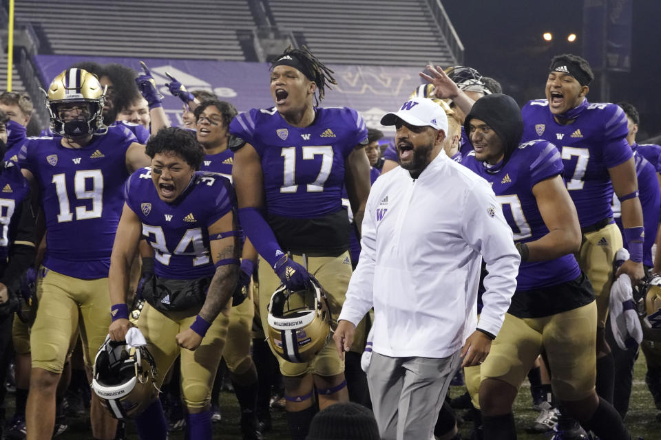 FILE - In this Nov. 28, 2020, file photo, Washington coach Jimmy Lake celebrates with his team after Washington defeated Utah 24-21 in an NCAA college football game in Seattle. Washington begins the 2021 season as one of the favorites in the Pac-12 North Division, while also trying to erase the bad taste of how last year ended when a COVID-19 outbreak brought a sudden end to an already truncated schedule. (AP Photo/Ted S. Warren, File)