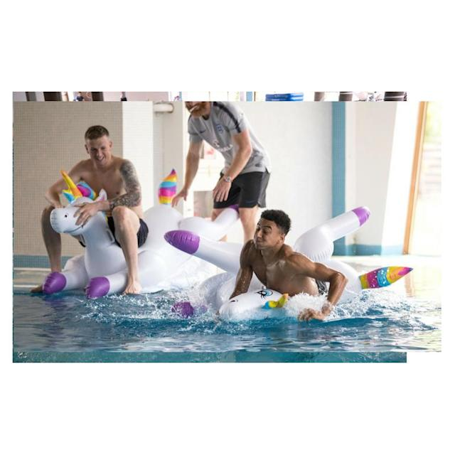 Jesse Lingard and Jordan Pickford play with inflatable unicorns in the pool during a recovery session at the ForRestMix Hotel in Repino (REX)