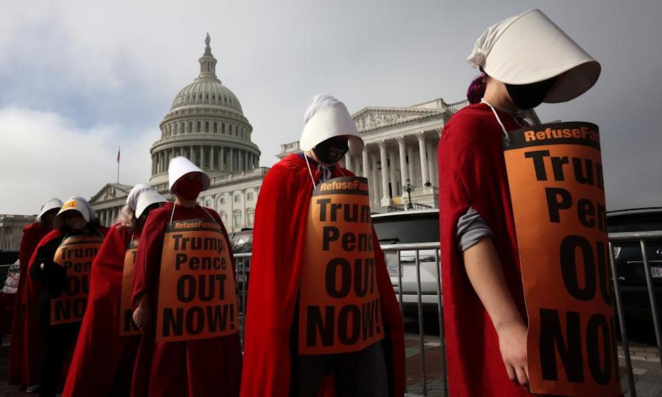 Protesters with the 'Handmaids Brigade' march outside the US Capitol after a hearing held by the senate judiciary committee to vote on the nomination of judge Amy Coney Barrett.