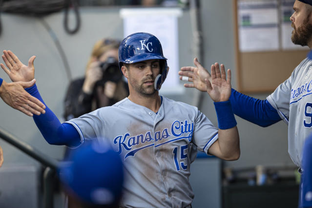 Kansas City Royals' Whit Merrifield is congratulated by teammates after scoring a run on a single by teammate Cheslor Cuthbert off Seattle Mariners starting pitcher Tayler Scott during the first inning of a baseball game, Monday, June 17, 2019, in Seattle. (AP Photo/Stephen Brashear)