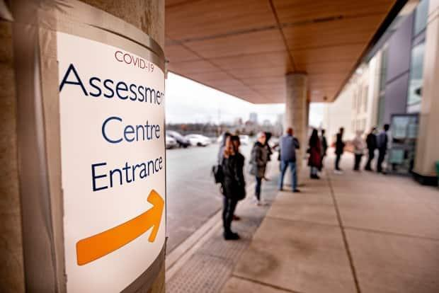 People line up outside a COVID-19 assessment centre in Brampton earlier this year. (Craig Chivers/CBC - image credit)