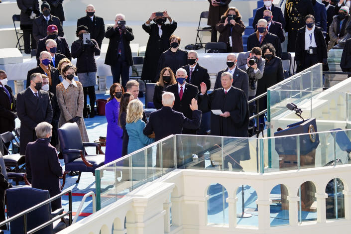 Joe Biden is sworn in as the 46th president of the United States by Chief Justice John Roberts as Jill Biden holds the Bible during the 59th Presidential Inauguration at the U.S. Capitol in Washington, Wednesday, Jan. 20, 2021. Former Vice President Mike Pence and his wife Karen loon on. (Kevin Dietsch/Pool Photo via AP)