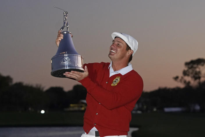 Bryson DeChambeau holds up his championship trophy after winning the Arnold Palmer Invitational golf tournament Sunday, March 7, 2021, in Orlando, Fla. (AP Photo/John Raoux)
