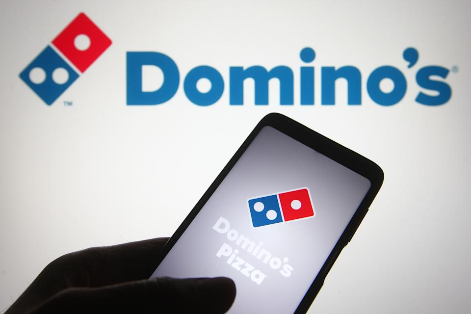 UKRAINE - 2021/05/01: In this photo illustration, Domino's Pizza logo of a pizza restaurant chain is seen displayed on a smartphone screen and in the background. (Photo Illustration by Pavlo Gonchar/SOPA Images/LightRocket via Getty Images)