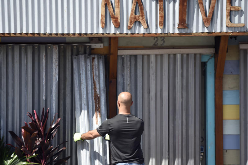 A worker affixes corrugated metal to the front of a business along the main drag in Folly Beach, S.C., on Tuesday, Sept. 3, 2019. Businesses and residents throughout the Charleston area continued to prepare structures for the arrival of Hurricane Dorian as the storm battered the Bahamas with life-threatening storm surge. (AP Photo/Meg Kinnard)