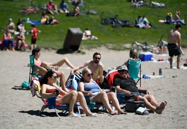 People enjoy the warm weather at Westboro Beach in Ottawa during the recent Victoria Day weekend. (Justin Tang/Canadian Press - image credit)