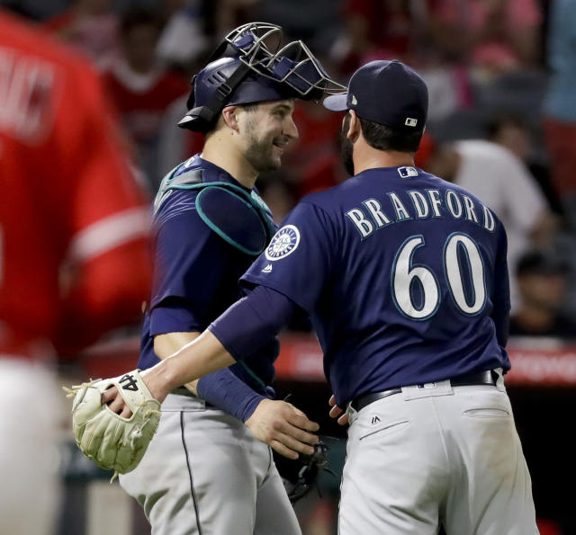 Seattle Mariners relief pitcher Chasen Bradford, right, and catcher Mike Zunino celebrate after their win against the Los Angeles Angels during a baseball game in Anaheim, Calif., Thursday, Sept. 13, 2018. (AP Photo/Chris Carlson)