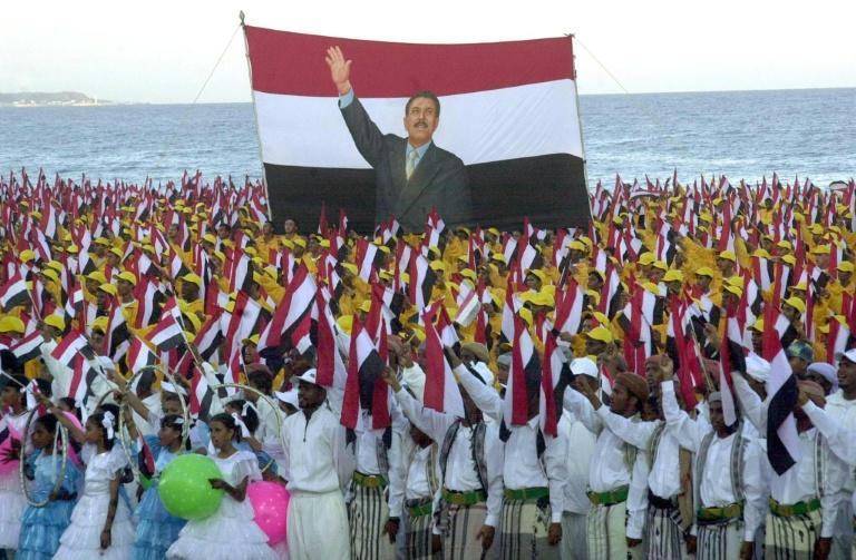 Yemenis holding national flags take part in celebrations of the 15th anniversary of the reunification of Yemen in the port city of Mukalla on May 22, 2005
