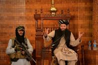 An imam speaks next to an armed Taliban fighter during Friday prayers at the Abdul Rahman Mosque in Kabul on August 20, 2021, following the Taliban's stunning takeover of Afghanistan