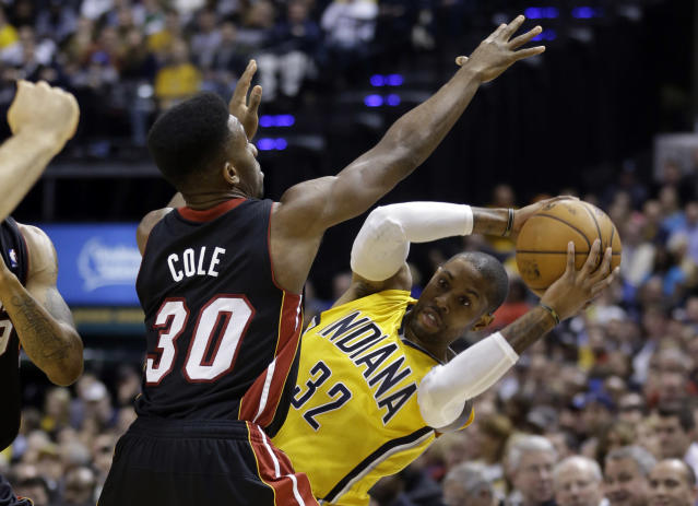 Indiana Pacers guard C.J. Watson, right, looks to make a pass around Miami Heat guard Norris Cole in the second half of an NBA basketball game in Indianapolis, Tuesday, Dec. 10, 2013. (AP Photo/Michael Conroy)