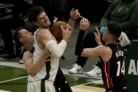 Miami Heat's Duncan Robinson fouls Milwaukee Bucks' Brook Lopez during the first half of an NBA basketball game Saturday, May 15, 2021, in Milwaukee. (AP Photo/Morry Gash)